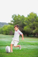 Boy kicking rugby ball