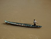 Fisherman on his boat paddling on the Mekong River in Luang Prabang Laos
