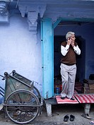 Man talking on cellphone at the entrance of his house