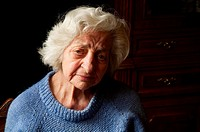 Portrait of old woman at home, looking at the camera. Close view.