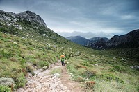 trekker ascending the Prat comellar Escorca, Tramuntana Mountains, Mallorca Balearic Islands Spain