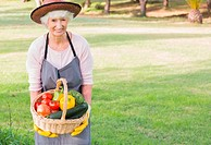 Smiling elderly woman carrying basket of vegetables wearing hat and apron