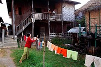 Burmese Woman hanging up laundry, Inle Lake, Shan states, Burma