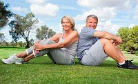 Portrait of older couple in sportswear back to back