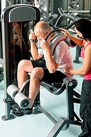 Mature man exercising with personal trainer