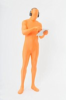 Mature man in orange zentai listening music and using digital tablet