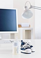 Desk with baby bottle and baby shoes