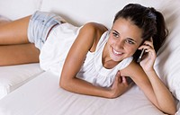 Teenage girl lying on white couch and using cell phone