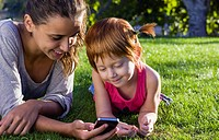 Spain, Teenage girl and girl using smart phone on grass, close up