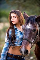 USA, Texas, Cowgirl standing with horse