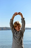 Germany, Bavaria, Boy raising arms, smiling, portrait
