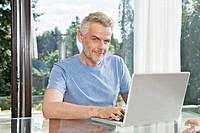 Germany, Berlin, Mature man sitting at table and using laptop