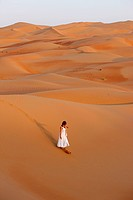Woman walking in Liwa desert, United Arab Emirates.