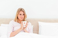 Woman in bed with a cup in hands, softly smiling while looking to the side sligh
