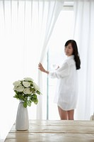 woman wearing white shirt and opening the white curtains