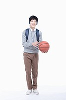 a male student with headphones playing with a basketball