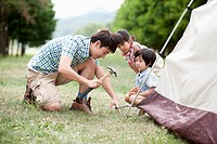 kids watching a father hammering to build a tent
