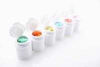white drug bottles filled up with different colours of medicine tablets