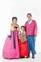 a girl standing with grandparents wearing Hanbok while holding a present