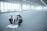 architect executives discussing with blueprints on the floor of an empty room