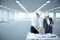 architect executives discussing with blueprints on a desk of an empty room