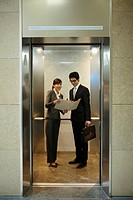 a businessman and woman discussing with documents in elevator