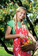 Smiling young woman in apple orchard