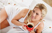 Smiling young woman drinking coffee in bed