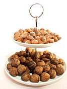 Tray with hazelnuts and walnuts on white background, close up