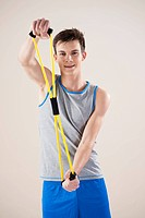 young man doing fitness exercises with a fitness strap