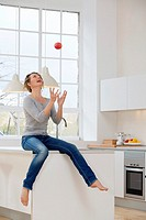 Healthy young woman throwing an apple into the air