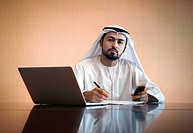 A Middle Eastern businessman in traditional Arabic dress at a desk in a boardroom with a laptop and holding a smartphone, signing some papers and look...