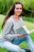 Young smiling woman holding her book while looking at the camera