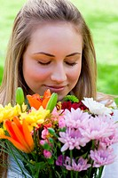 Young blonde girl closing her eyes while smelling a bunch of flowers
