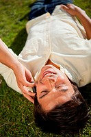 Close_up of a man making a call while using a phone as he lies on the grass