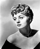 An intense picture of US actress Shelley Winters wearing a pearl necklace and an evening dress.