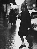 The French baby girl poetess, Minou Drouet, walking with an umbrella in her left hand and a bunch of flowers in her right hand. Paris, 1959