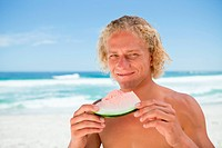 Smiling blonde man holding a piece of a watermelon while standing on the beach