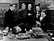 British actors Austin Trevor, John Henry Roberts, John Deverell and Harvey Braban looking at British actor Franklin Dyall lying with his head on the t...