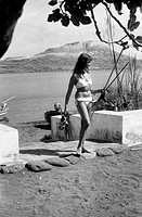 German tourist wearing a bikini and carrying the underwater fishing equipment on the beach of Vulcano Island in the Aeolian archipelago. Vulcano, 1960...