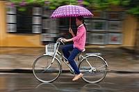 Vietnamese girl cycling in the rain, Hoi An, Vietnam