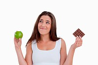Relaxed young woman holding an apple and chocolate