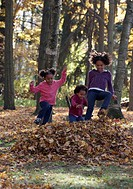 African American girls playing in autumn leaves