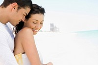 Hispanic couple hugging on beach