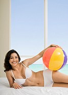 Hispanic woman holding beach ball on bed