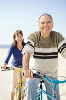 Couple sitting on bicycles on beach