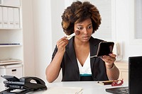 African American businesswoman applying makeup in office
