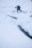 Hiker snow shoeing in rural landscape