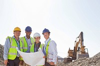 Business people reading blueprints in quarry