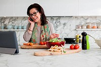 Woman on cell phone and cooking